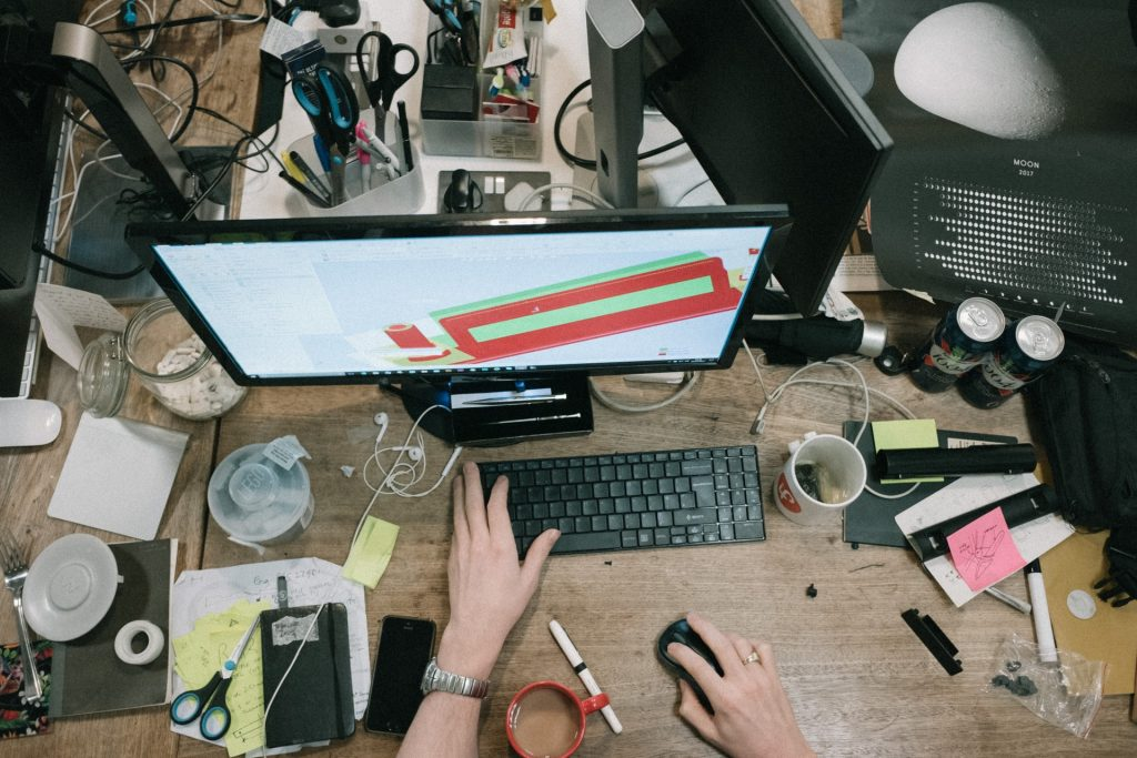 Work in an uncluttered environment - man working at messy desk