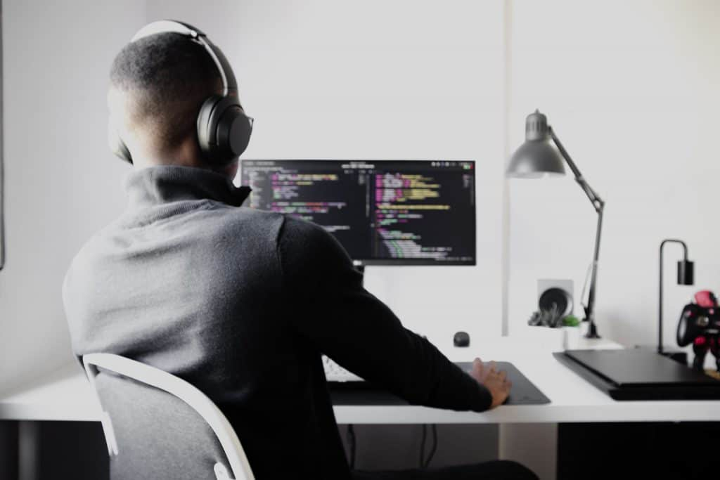 Man coding at desk while focused