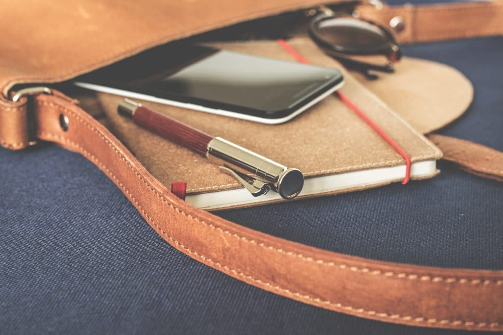 woman's purse with notebook, pen and phone