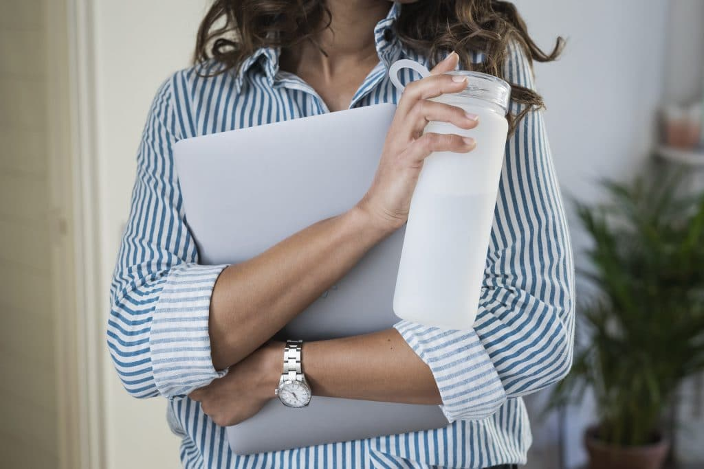 woman taking a water break and holding her laptop