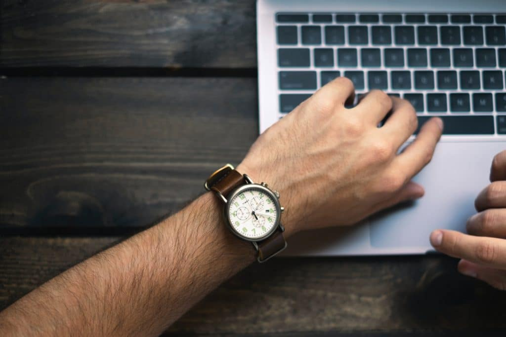 man checking time while working on computer