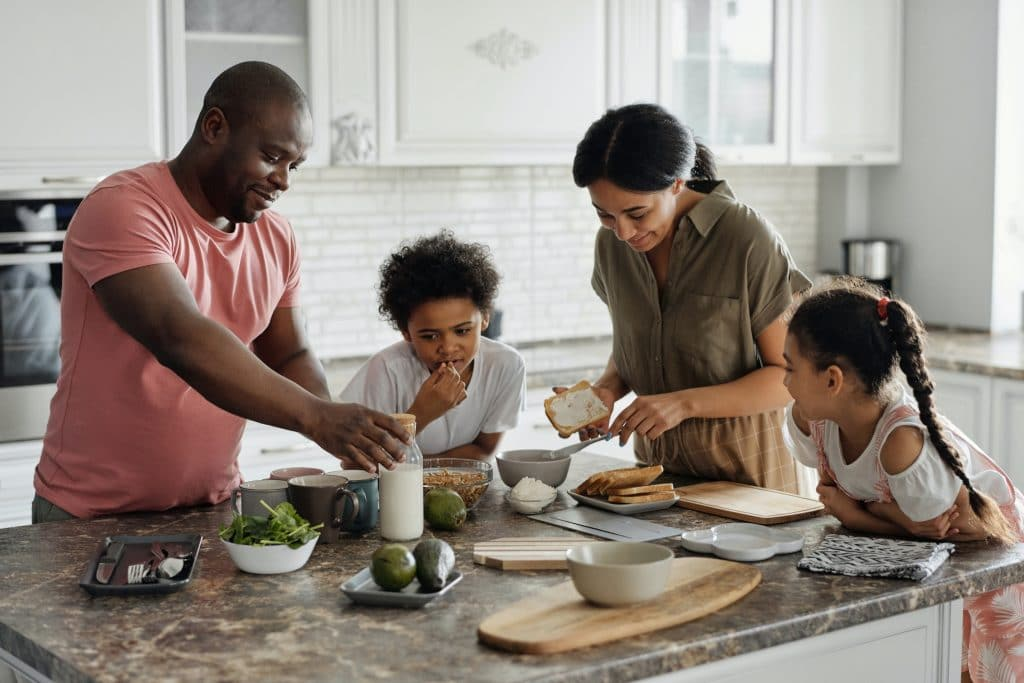 Family preparing breakfast together in the kitchen