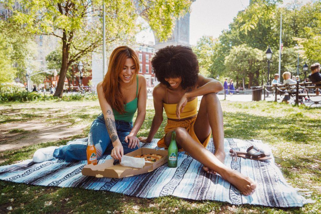 two women enjoying pizza in a park