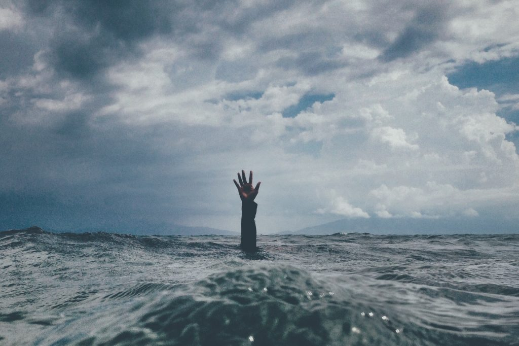 Hand reaching up out of the ocean