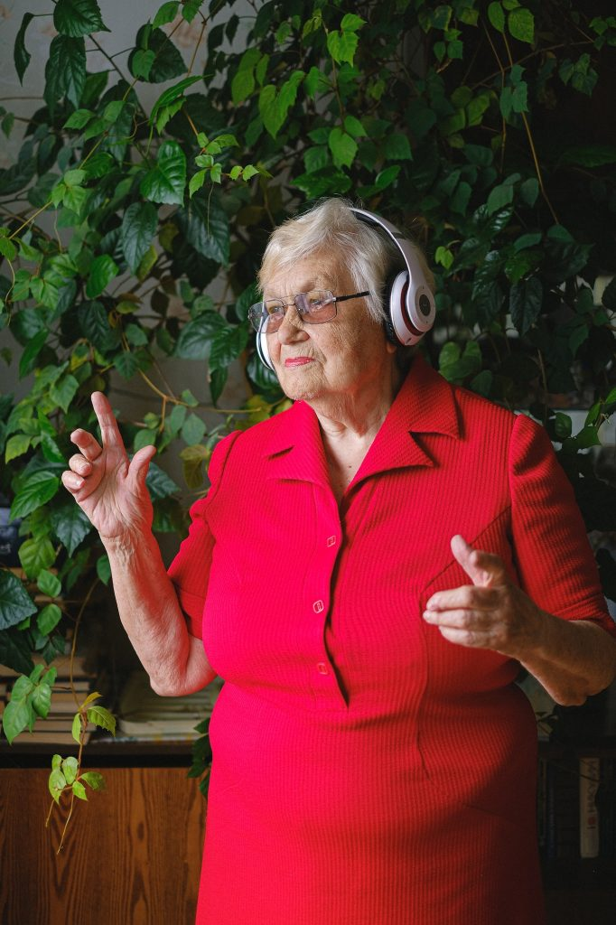 elderly woman listening to music with headphones and dancing