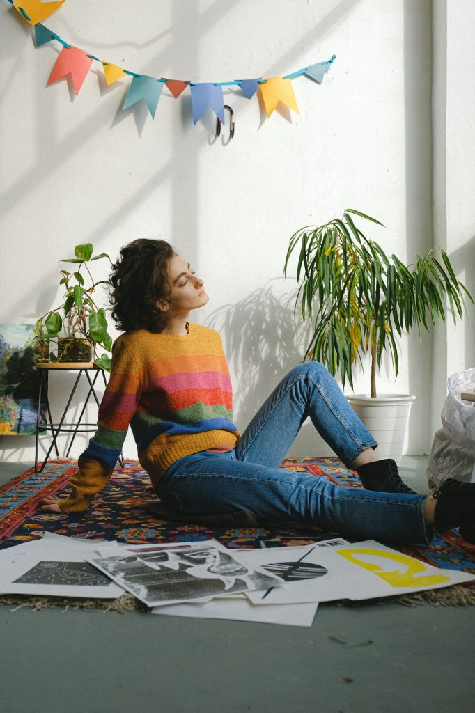 woman sittinf on the floor of apartment surrounded by drawings
