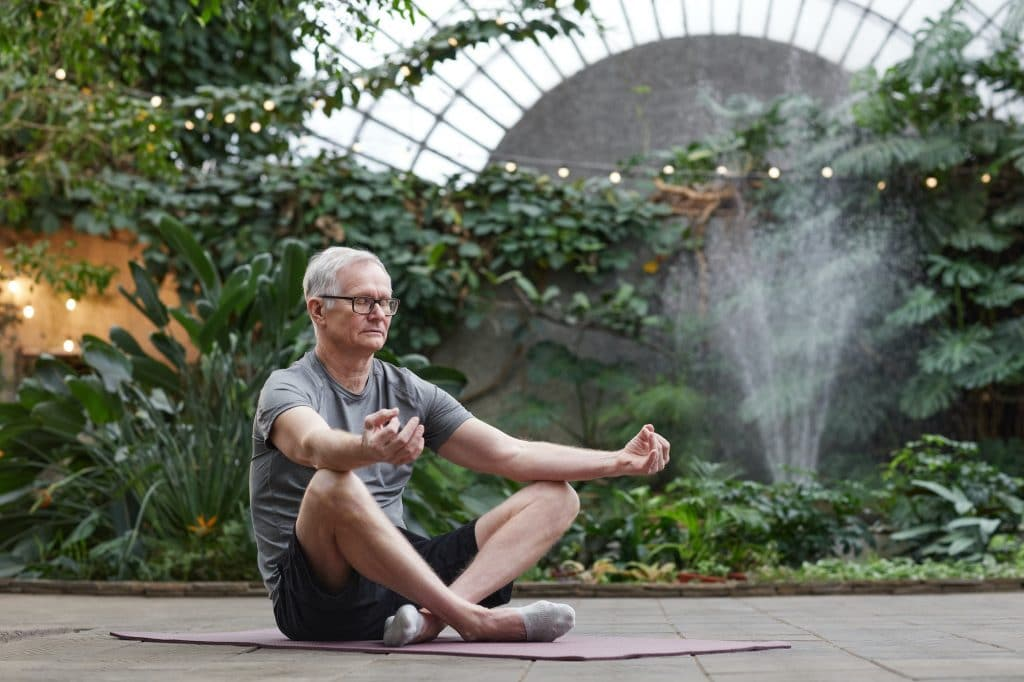 middle-aged man meditating in garden