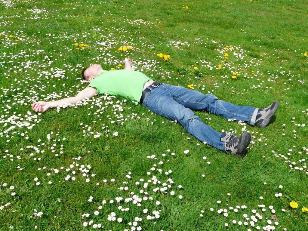 man relaxing on grass with flowers
