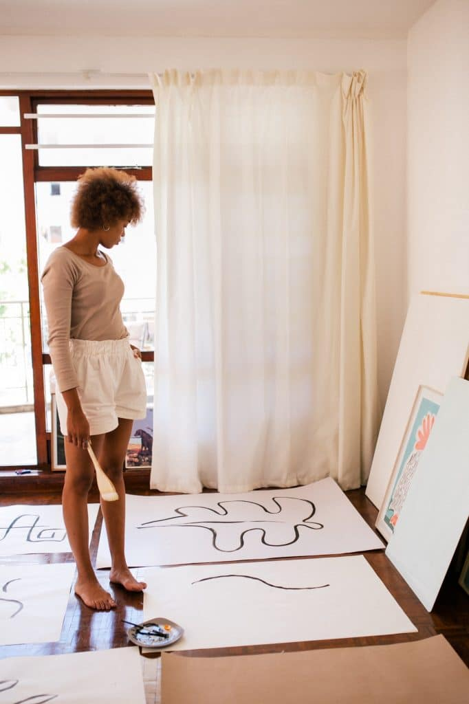 female artist contemplating her paintings in apartment