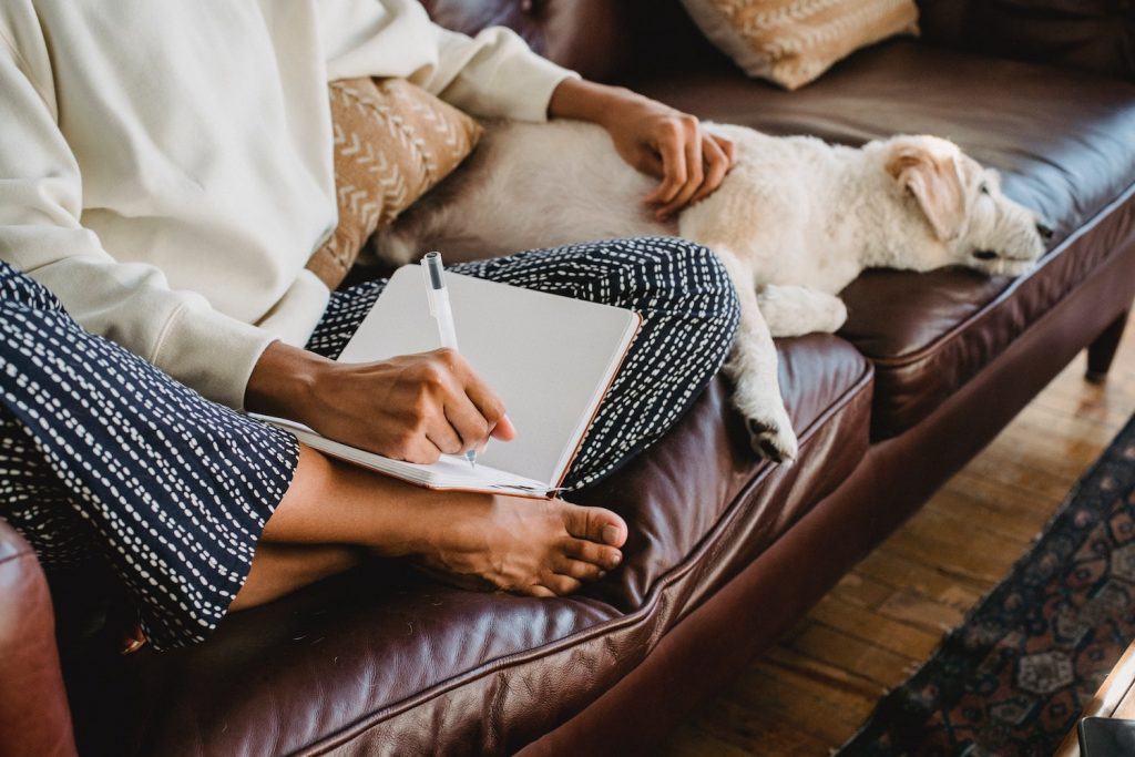 woman taking notes on couch while dog relaxes beside her