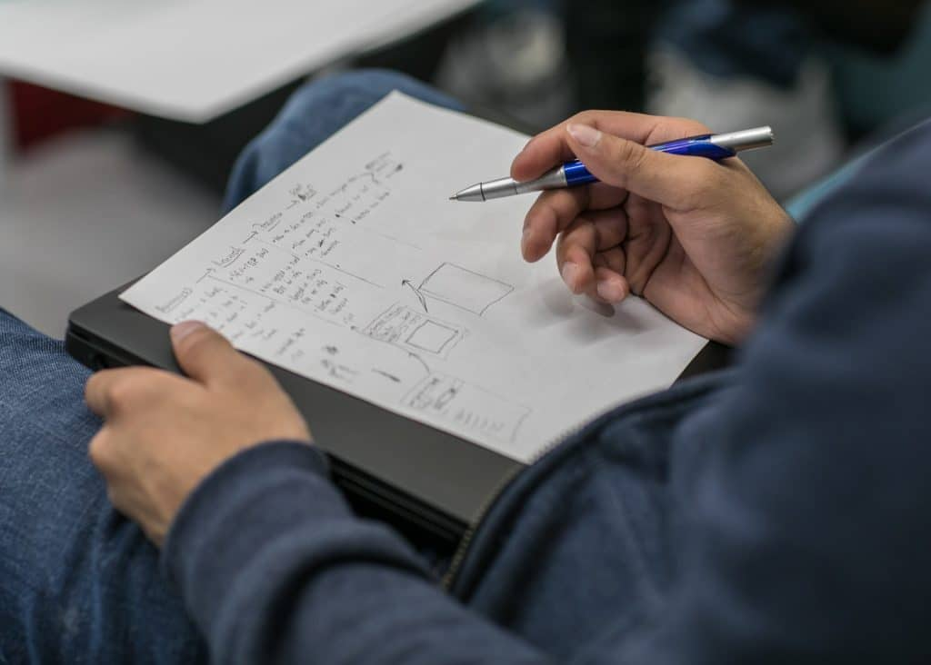 Man writing out his notes to condense and process the information