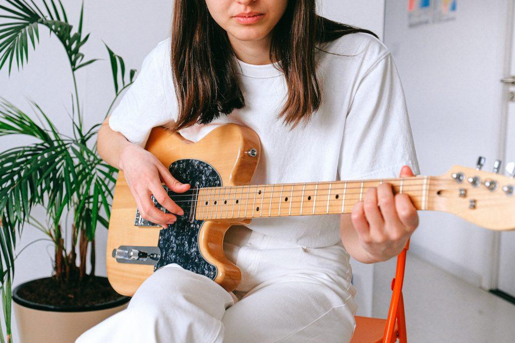 Woman practising guitar at home as hobby