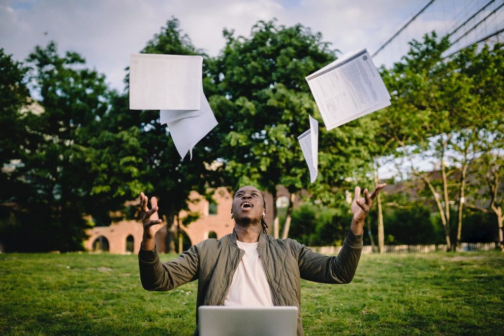 College student celebrating success throwing papers in air