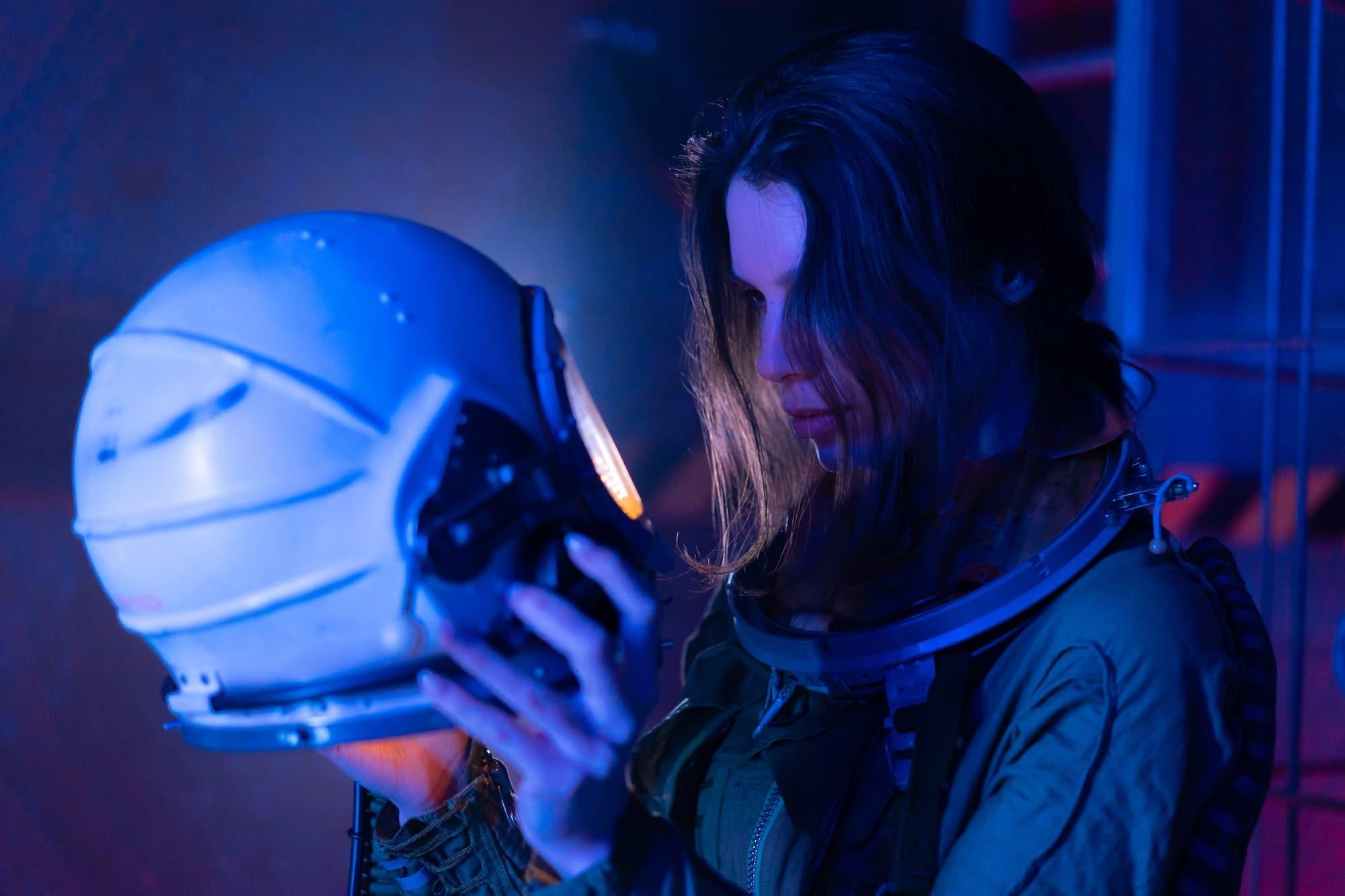 Female astronaut looking into helmet blue light truth